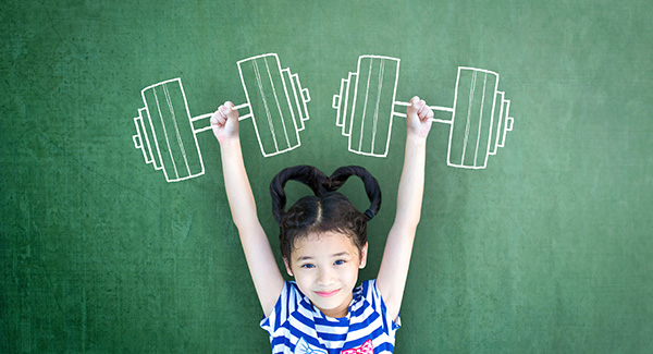 Child with arms up standing infront of a chalkborad with drawn bar bells