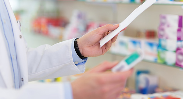 close up of pharmacist holding prescriptions