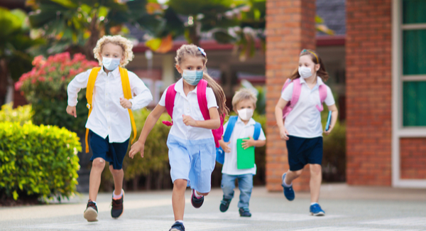 Young children running outside with facemasks
