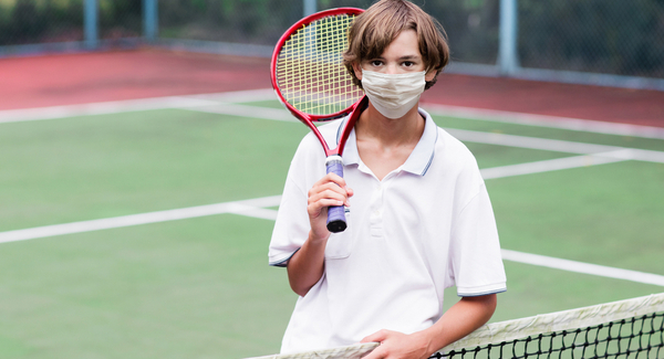 Young Boy wearing facemask while playing tennis