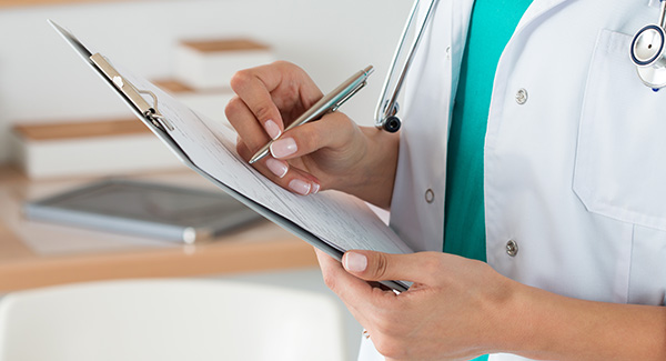 physician writing on a clipboard